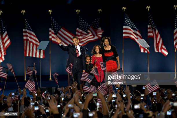 Democratic presidentelect Barack Obama waves to supporters flanked by his wife Michelle and daughters Malia Ann right and Sasha ahead of making his...