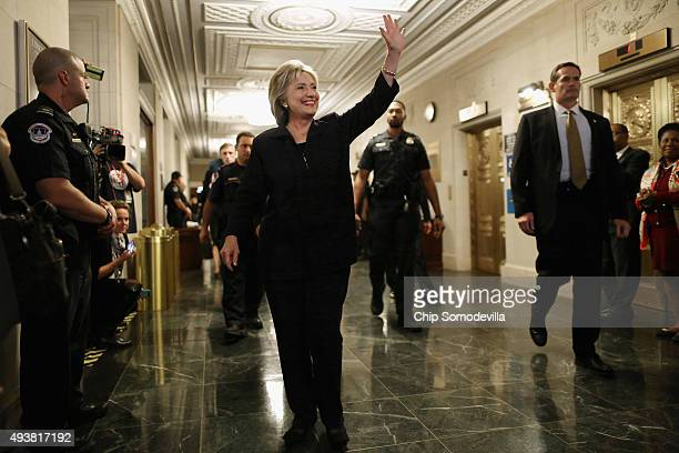 Democratic presidential candidate and former Secretary of State Hillary Clinton waves goodbye to journalists after testifying to the House Select...