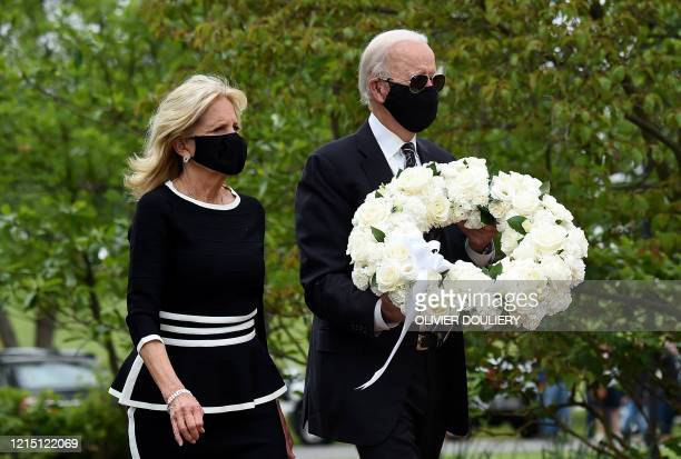 TOPSHOT Democratic presidential candidate and former US Vice President Joe Biden with his wife Jill Biden pay their respects to fallen service...