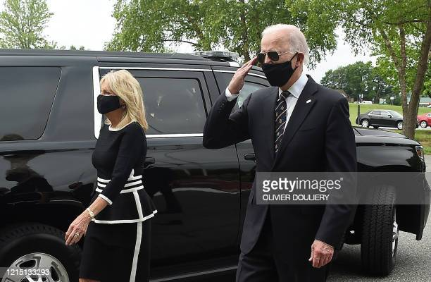 TOPSHOT Democratic presidential candidate and former US Vice President Joe Biden salutes veterans while walking with his wife Jill at the Delaware...