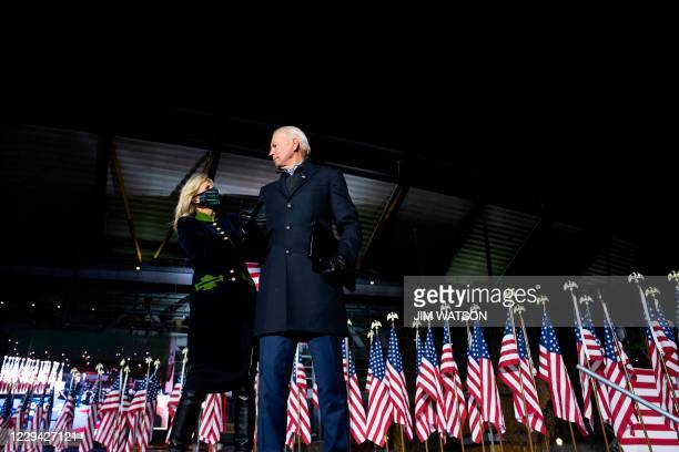 Democratic Presidential candidate and former US Vice President Joe Biden, alongside wife Jill Biden, gesture to supporters after speaking during a...