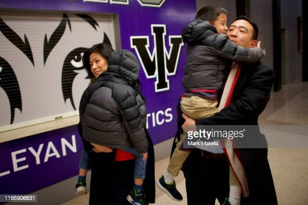 Democratic presidential candidate Andrew Yang and wife Evelyn carry their sons to the campaign bus following a rally at Iowa Wesleyan University on...