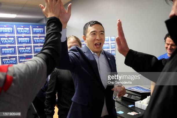 Democratic presidential candidate Andrew Yang gives high-fives to campaign volunteers following a town hall meeting at Penn Central Mall January 25,...