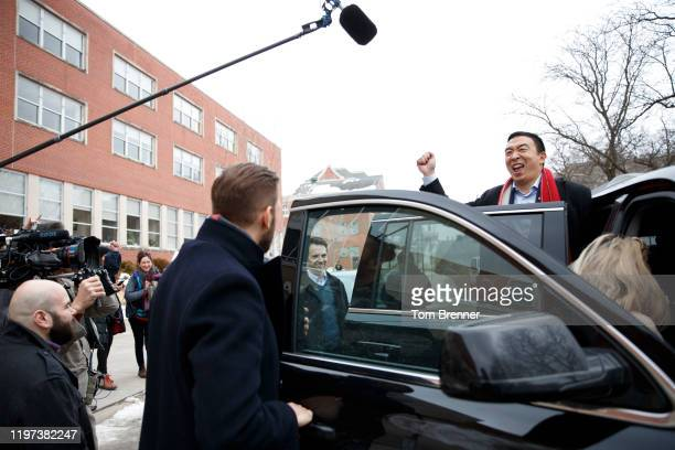 Democratic presidential candidate Andrew Yang, right, makes a face to members of the news media before stepping to his car, following a campaign...