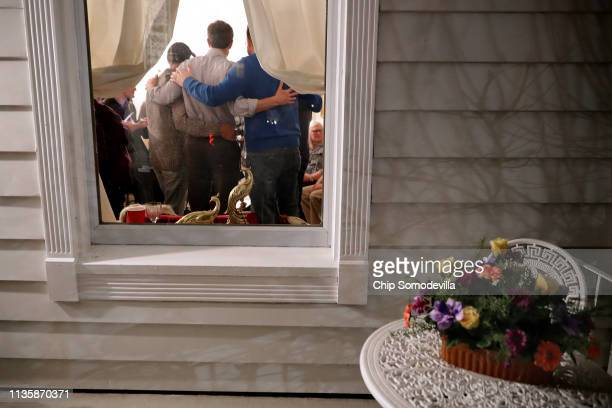 Democratic presidential candidate Beto O'Rourke is seen through the front window of Randy Naber's home as he poses for photographs with supporters...