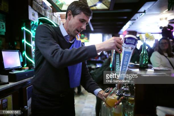 Democratic presidential candidate Beto O'Rourke pours a beer for a customer at Yock's Landing during his second day of campaigning for the 2020...