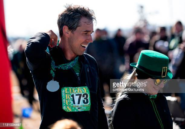 Democratic presidential candidate Beto O'Rourke receives a medal after finishing the Lucky Run 5k race on March 16 2019 in North Liberty Iowa...