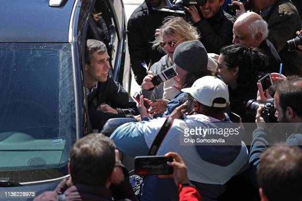 Democratic presidential candidate Beto O'Rourke talks to supporters from behind the wheel of his minivan following a rally with state senate...