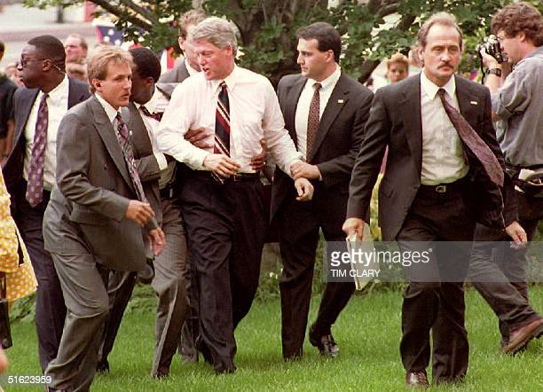 Democratic presidential candidate Bill Clinton is escorted away from a crowd by US Secret Service agents 20 July after an antiabortion protester...