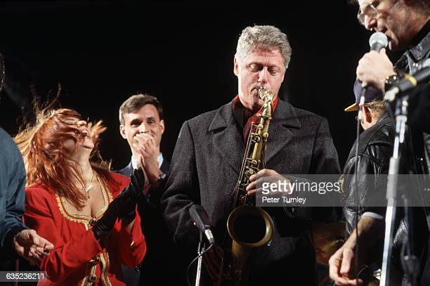 Democratic presidential candidate Bill Clinton plays saxophones while some of his supporters sing and dance
