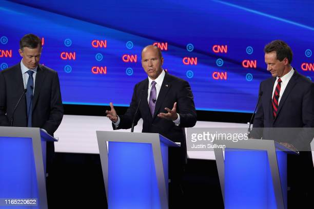 Democratic presidential candidate former Maryland congressman John Delaney speaks while former Colorado governor John Hickenlooper and Montana Gov....
