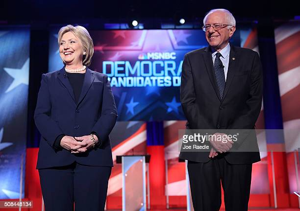 Democratic presidential candidate former Secretary of State Hillary Clinton and US Sen Bernie Sanders stand next to each other at the start of their...