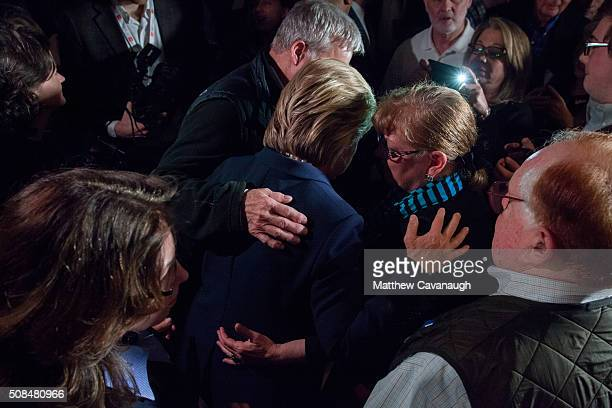 Democratic presidential candidate former Secretary of State Hillary Clinton is embraced by supporters at a debate watching party on February 4 2016...