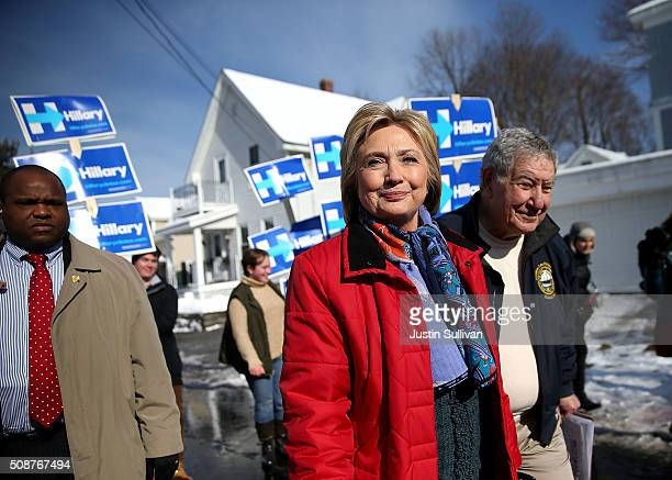 Democratic presidential candidate former Secretary of State Hillary Clinton walks with New Hampshire state senator Lou D'Allesandro as they knock on...