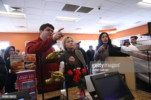 Democratic presidential candidate former Secretary of State Hillary Clinton prepares to order food at a Dunkin Donuts with New Hampshire state...
