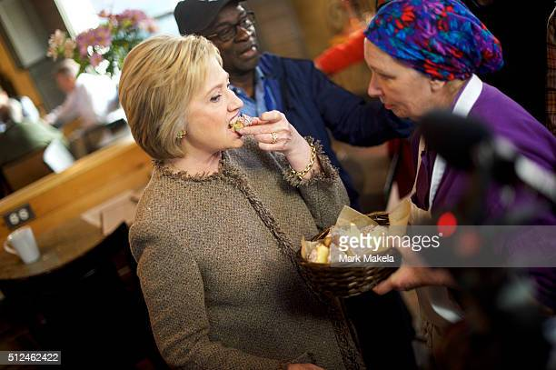Democratic Presidential candidate former Secretary of State Hillary Clinton samples cake during a visit to Saffron's Cafe Bakery February 26 2016 in...