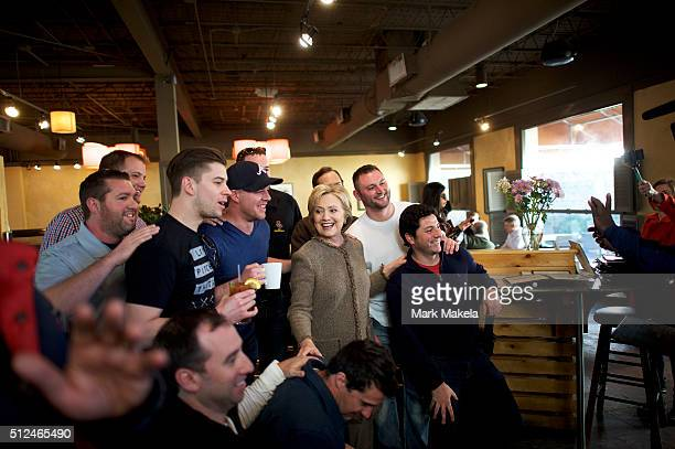Democratic Presidential candidate former Secretary of State Hillary Clinton gathers for a group photo with patrons while visiting Saffron's Cafe...