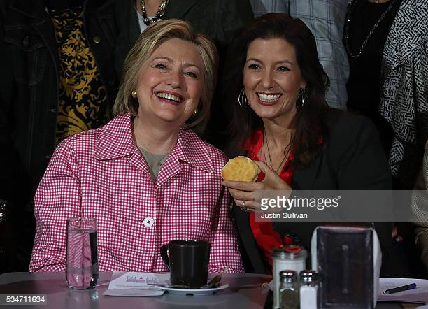 Democratic presidential candidate former Secretary of State Hillary Clinton and Oakland mayor Libby Schaaf hold a biscuit during a roundtable...