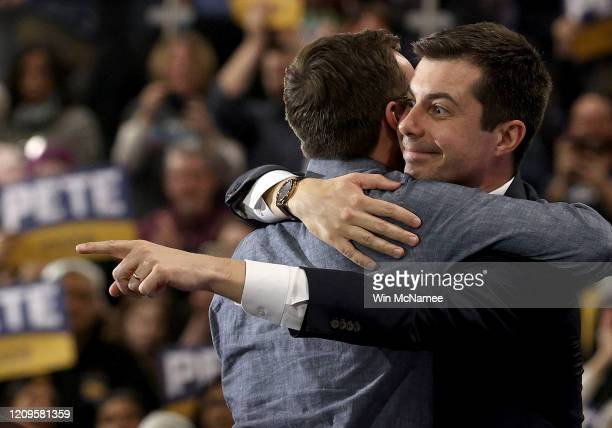 Democratic presidential candidate former South Bend, Indiana Mayor Pete Buttigieg hugs his husband Chasten and points to a supporter in the crowd...