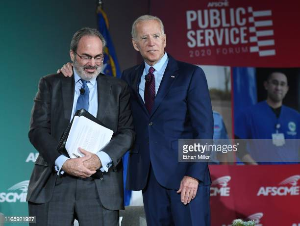 Democratic presidential candidate former US Vice President Joe Biden puts his arm around moderator and The Nevada Independent editor Jon Ralston as...