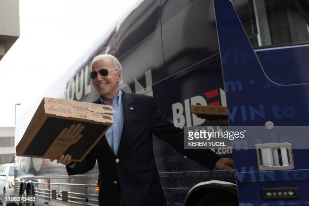 Democratic presidential candidate former Vice President Joe Biden carries a pizza box before speaking at a stop event in Des Moines Iowa on February...