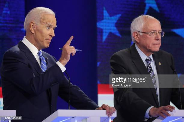Democratic presidential candidate former Vice President Joe Biden speaks as Sen Bernie Sanders looks on during the second night of the first...