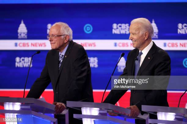 Democratic presidential candidate former Vice President Joe Biden smiles as Sen Bernie Sanders looks on during the Democratic presidential primary...