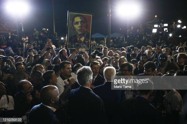 Democratic presidential candidate former Vice President Joe Biden greets supporters as a poster of former President Barack Obama is held aloft at a...