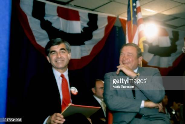 Democratic Presidential candidate Governor of Massachusetts Michael Dukakis sits with Congressman Dan Rostenkowski at a campaign rally during a swing...