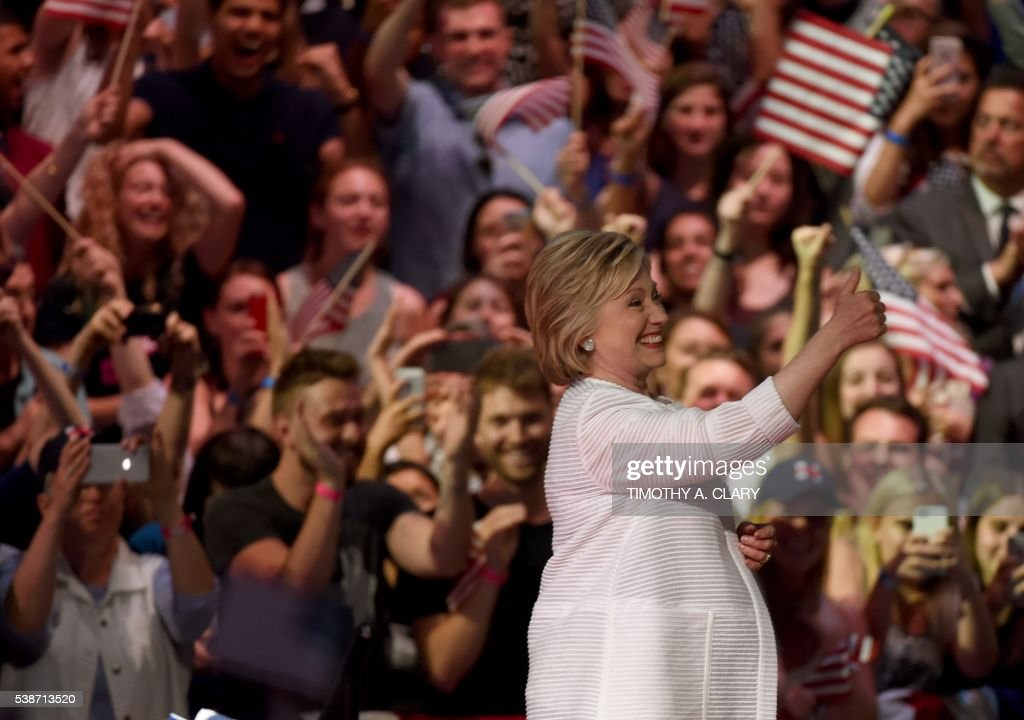 TOPSHOT - Democratic presidential candidate Hillary Clinton acknowledges celebratory cheers from the crowd during her primary night event at the Duggal Greenhouse, Brooklyn Navy Yard, June 7, 2016 in New York. Hillary Clinton hailed a historical 'milestone' for women as she claimed victory over rival Bernie Sanders in the Democratic White House nomination race. 'Thanks to you, we've reached a milestone,' she told cheering supporters at a rally in New York. 'The first time in our nation's history that a woman will be a major party's nominee.' A. CLARY
