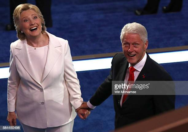 Democratic presidential candidate Hillary Clinton and her husband former US President Bill Clinton acknowledges the crowd at the end of the fourth...