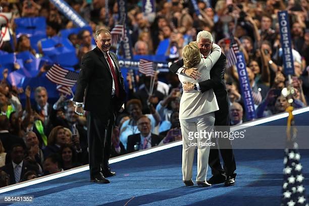 Democratic presidential candidate Hillary Clinton and husband former US President Bill Clinton embrace as US Vice President nominee Tim Kaine looks...