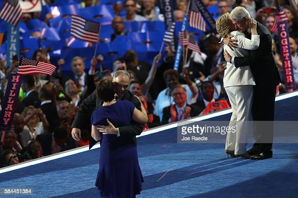 Democratic presidential candidate Hillary Clinton and husband former US President Bill Clinton embrace as US Vice President nominee Tim Kaine and his...