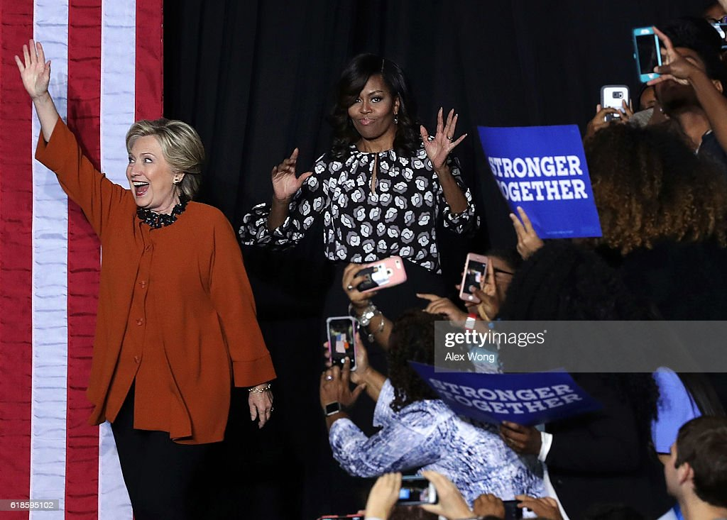 Democratic presidential candidate Hillary Clinton (L) and U.S. first lady Michelle Obama (R) greet supporters during a campaign event at the Lawrence Joel Veterans Memorial Coliseum October 27, 2016 in Winston-Salem, North Carolina. The first lady joined Clinton for the first time to campaign for the presidential election.