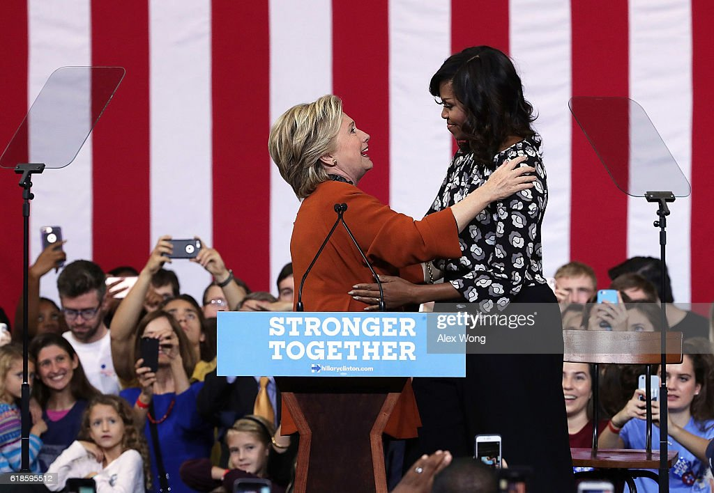 Democratic presidential candidate Hillary Clinton (L) and U.S. first lady Michelle Obama (R) share a moment as supporters look on during a campaign event at the Lawrence Joel Veterans Memorial Coliseum October 27, 2016 in Winston-Salem, North Carolina. The first lady joined Clinton for the first time to campaign for the presidential election.