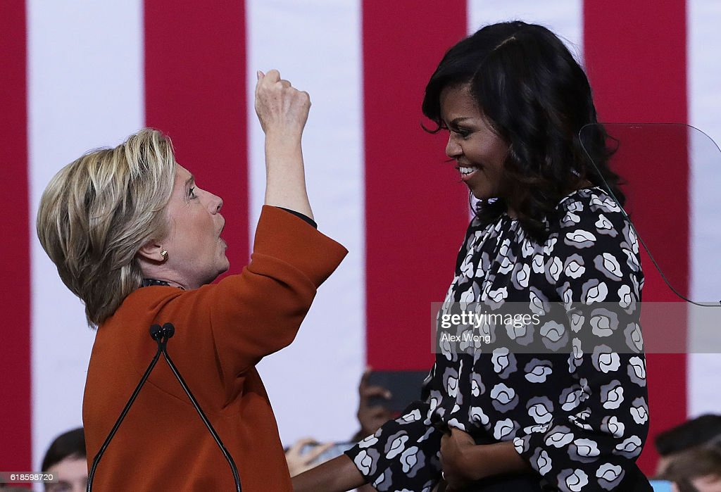 Democratic presidential candidate Hillary Clinton (L) and U.S. first lady Michelle Obama (R) share a moment during a campaign event at the Lawrence Joel Veterans Memorial Coliseum October 27, 2016 in Winston-Salem, North Carolina. The first lady joined Clinton for the first time to campaign for the presidential election.