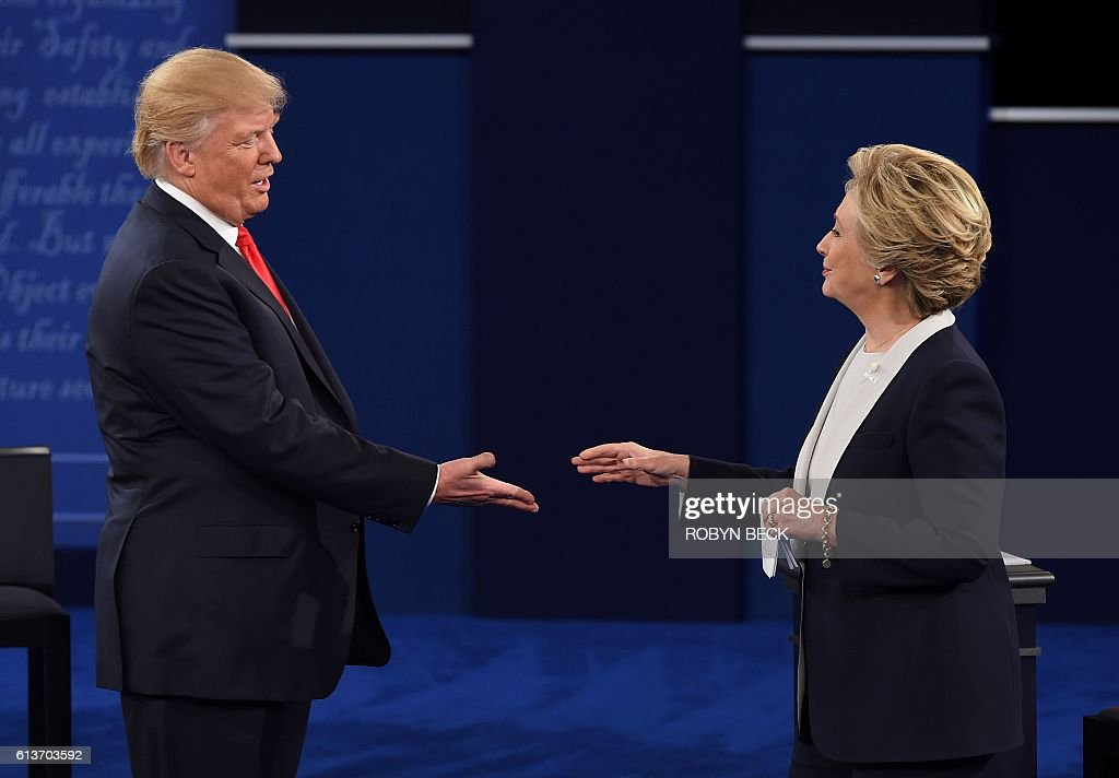 Democratic presidential candidate Hillary Clinton and US Republican presidential candidate Donald Trump shakes hands after the second presidential debate at Washington University in St. Louis, Missouri, on October 9, 2016. / AFP / Robyn Beck