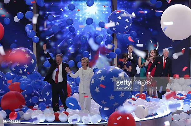 Democratic presidential candidate Hillary Clinton and US Vice President nominee Tim Kaine stand with their families on stage at the end of the fourth...