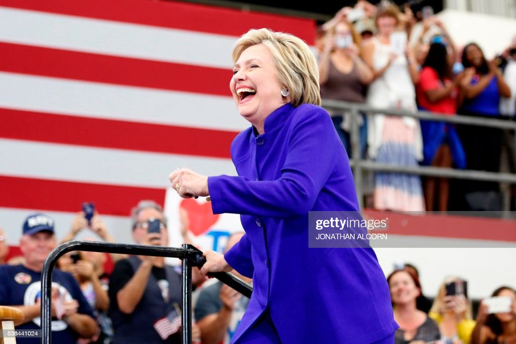 TOPSHOT - Democratic presidential candidate Hillary Clinton arrives on stage for a rally at Long Beach City College on the final day of California campaigning, June 6, 2016 in Long Beach, California. Hillary Clinton has received commitments from enough delegates to clinch the Democratic presidential nomination, according to the Associated Press and US networks, ensuring she will be the first woman to lead a major US party in the race for the White House. / AFP / JONATHAN