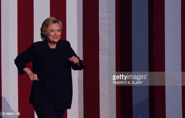 TOPSHOT Democratic presidential candidate Hillary Clinton arrives on stage during a rally at Ohio State University in Columbus Ohio October 102016 /...