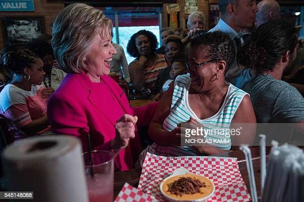 US Democratic presidential candidate Hillary Clinton greets a patron at Midwood Smokehouse in Charlotte North Carolina on July 5 2016 US President...