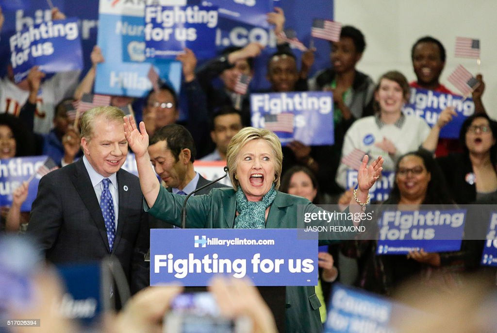 Democratic presidential candidate Hillary Clinton greets the crowd after an introduction by Seattle Mayor Ed Murray (L) during a rally at Rainer Beach High School in Seattle on March 22, 2016. / AFP / Jason Redmond