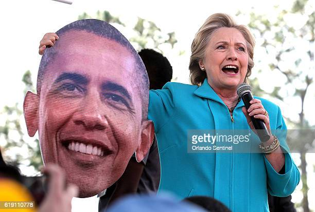 Democratic presidential candidate Hillary Clinton jokes with a giant image of Pres Barack Obama that was handed to her by a supporter while she...
