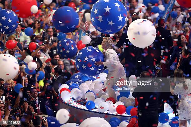 Democratic presidential candidate Hillary Clinton plays with balloons on stage at the end of the fourth day of the Democratic National Convention at...