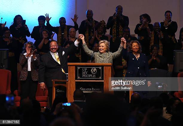 Democratic Presidential candidate Hillary Clinton raises her arms with pastor Bill Adkins during church services at The Greater Imani Cathedral of...