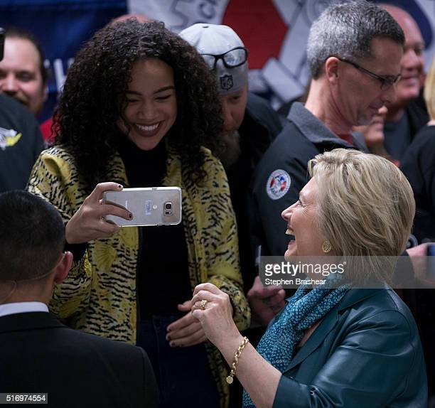 Democratic presidential candidate Hillary Clinton shares a laugh with a supporter after taking selfie at a labor rally on March 22 2016 in Everett...