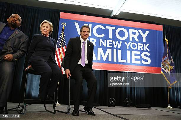 Democratic presidential candidate Hillary Clinton sits with New York Governor Andrew Cuomo at a rally with after he signed a law that will gradually...