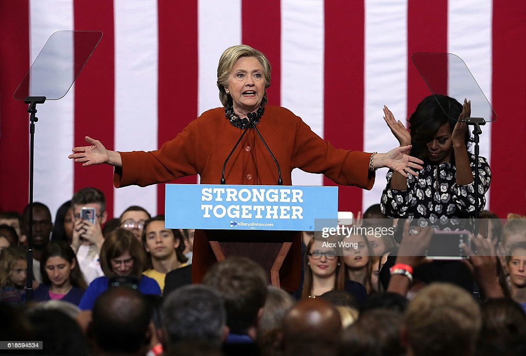Democratic presidential candidate Hillary Clinton (L) speaks as U.S. first lady Michelle Obama (R) listens during a campaign event at the Lawrence Joel Veterans Memorial Coliseum October 27, 2016 in Winston-Salem, North Carolina. The first lady joined Clinton for the first time to campaign for the presidential election.