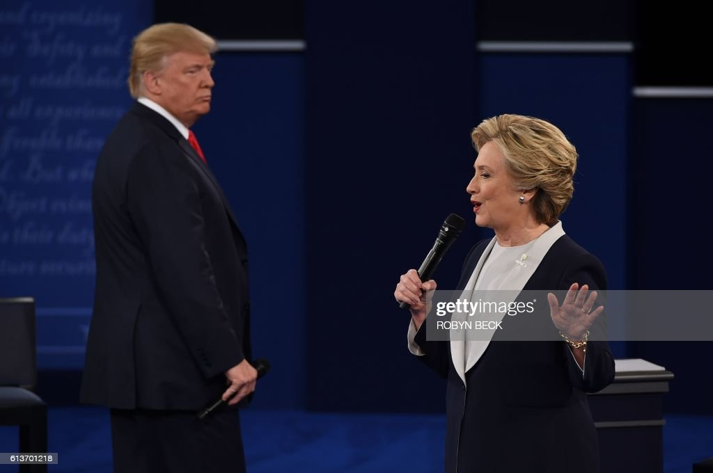 Democratic presidential candidate Hillary Clinton (R) speaks as US Republican presidential candidate Donald Trump listens during the second presidential debate at Washington University in St. Louis, Missouri, on October 9, 2016. / AFP PHOTO / Robyn Beck