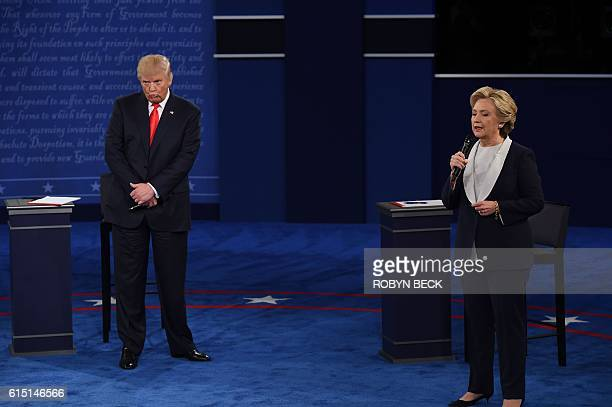 US Democratic presidential candidate Hillary Clinton speaks as US Republican presidential candidate Donald Trump listens during the second...